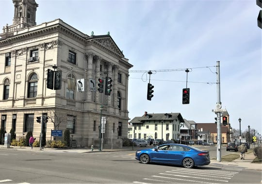Vehicles and pedestrians pass by City Hall in downtown Elmira on Monday. City Hall is still open for business despite the coronavirus threat.