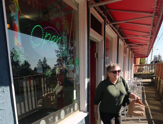 Carol Jackson exits Hi-Lo's 15th Street Cafe in Bremerton with a to-go order in hand on Monday.