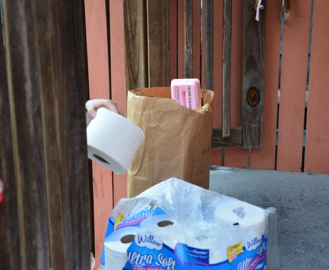 A woman takes  a roll of toilet paper with her bag of food on Monday morning. St. Mary's Helping Hands  in Rockledge, a local food pantry, was giving out bags of food containing canned good, pasta, sauce, cereal, meat  and one roll of bathroom tissue for as long as the supplies last.