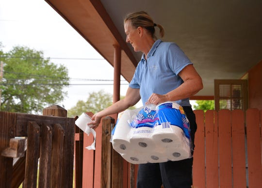 Amy Tidd, volunteer at St. Mary's Helping Hands in Rockledge, offers a roll of toilet paper along wtih a bag of food to a woman who came to the food pantry in search of help on March 16. The pantry is open Monday, Wednesday and Friday from 9 a.m. to 11 a.m.