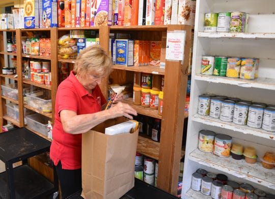 Volunteer Donalene McDonald fills up a grocery bag with food at St. Mary's Helping Hands in Rockledge. On Monday, the outreach ministry,(open Monday, Wednesday and Friday) was offering canned good, pasta, sauce, cereal, meat -- and one roll of bathroom tissue, as long as the supplies last.