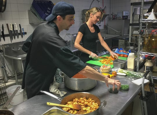 Chef Tony Durso and sous chef Kristi Cullinan of The Green Leaf in Palm Bay prepare oven-ready meals that will be delivered Tuesday.