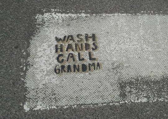 Message on a crosswalk: A health advisory is seen stenciled at Spruce and South Willard streets in Burlington on March 16, 2020.