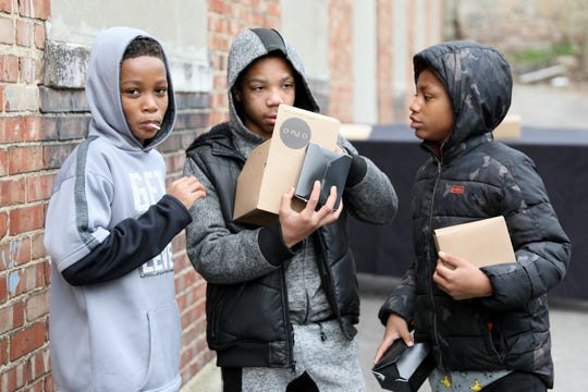 Children open their school lunch boxes after picking them up, Monday, March 16, 2020, at O Pie O's distribution center in Lower Price Hill. They have committed to offering 25 school lunches from 11 a.m. to noon, Monday through Friday.