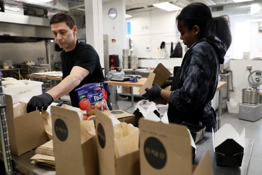 Lou Ginocchio, left, and Shona Wright, right, pack school lunches, Monday, March 16, 2020, at O Pie O's distribution center in Lower Price Hill. They have committed to offering 25 school lunches from 11 a.m. to noon, Monday through Friday.