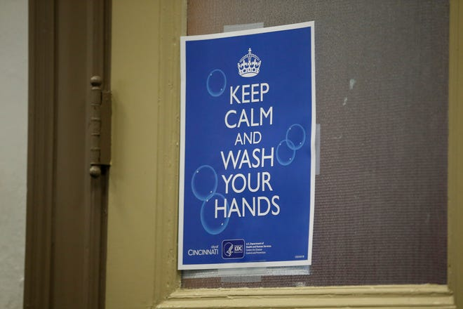 A sign posted encourages hand washing during a joint briefing from the City of Cincinnati and Hamilton County at city hall in downtown Cincinnati on Monday, March 16, 2020.