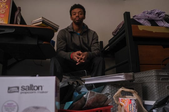 Michael Hunter poses for a photo with his packed up belongings at the 1mpact House in the University of Cincinnati's Stratford Heights housing complex in University Heights, Monday, March 16, 2020.
