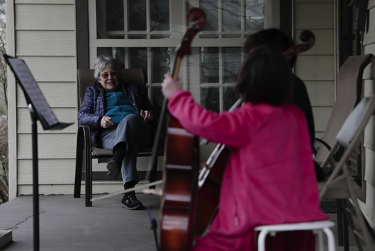 Helena Schlam, left, listens as her neighbors, Taran Tien, second from right, and Calliope Tien, right, play cello on her front porch on Monday, March 16, 2020, in Columbus, Ohio. The siblings decided to play a concert for Schlam because she was self-isolating due to the ongoing COVID-19 pandemic.
