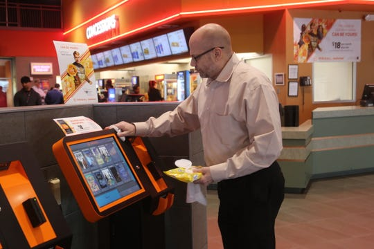 Regal Clarksville general manager Curtis Ewing sanitizes a movie kiosk at the theater on Tiny Town Road on Monday, March 16, 2020, as the theater responds to the coronavirus outbreak.