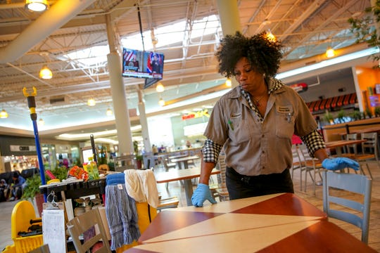 Mall house keeping worker Laureen Mille wipes down and adjusts tables in the food court at Governor's Square Mall in Clarksville, Tenn., on Monday, March 16, 2020.