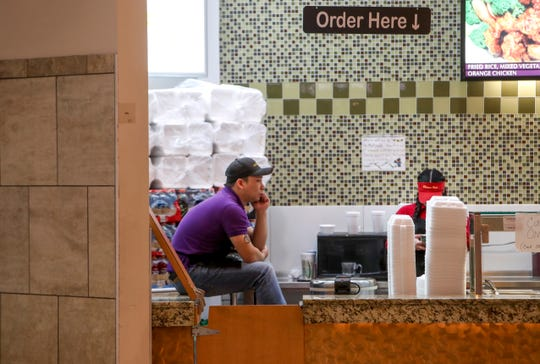 China Wok employees wait around during a slow time in the mall at Governor's Square Mall in Clarksville, Tenn., on Monday, March 16, 2020.