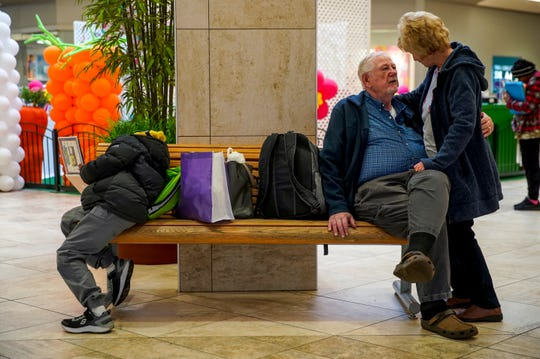 John Reilly, right, pulls his long time partner Sharon Hudson in close while the couple peruses a barren Mall on the same bench that Najir Waymyers, 10, left, reads a book filled with Spongebob cartoons at Governor's Square Mall in Clarksville, Tenn., on Monday, March 16, 2020.