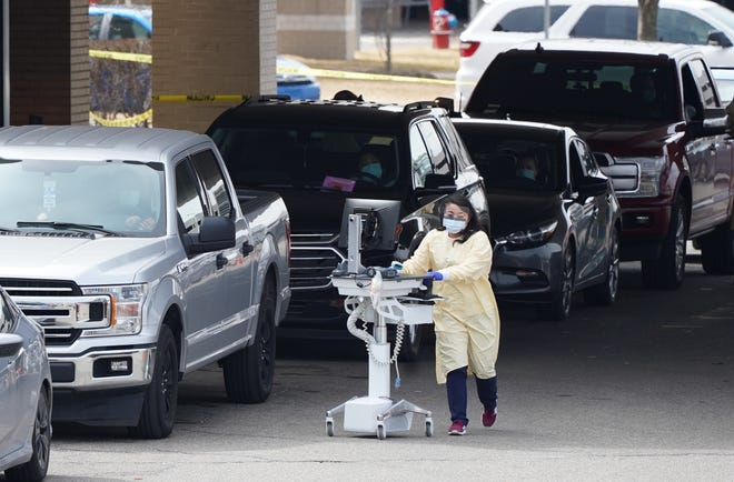 Medical staff talks with people in their cars that have driven to the Beaumont Health curbside screening for COVID-19 at Beaumont Hospital in Royal Oak on Monday, March 16, 2020.