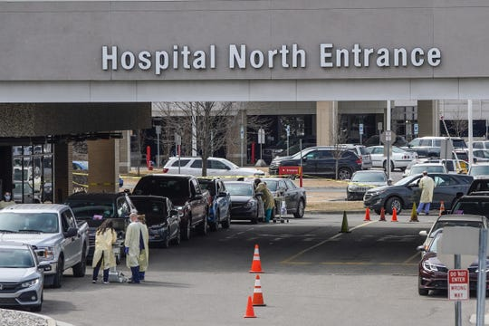 Medical staff talks with people in their cars that have driven to the Beaumont Health curbside screening for COVID-19 at Beaumont Hospital in Royal Oak on March 16, 2020.