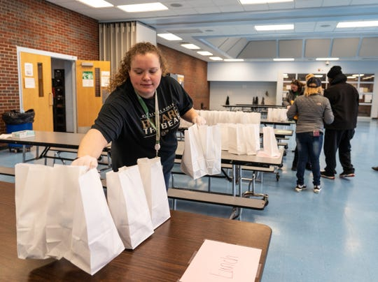 West Bloomfield School District ParaPro Melissa Gonzalez stocks a table with lunches to be picked up at Roosevelt Elementary School as the district remains closed due to COVID-19 pandemic on Monday, March 16, 2020 at Roosevelt Elementary School in Keego Harbor.