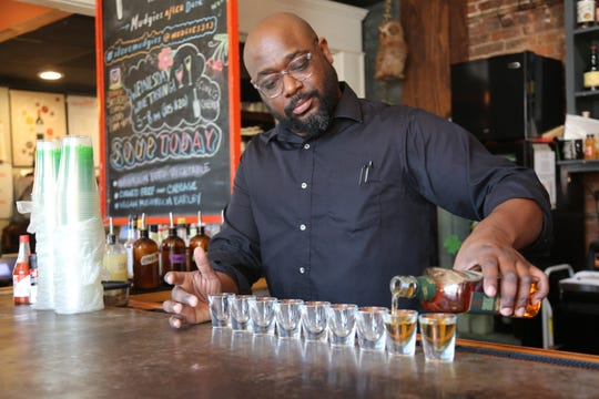 Mudgie's Deli bartender Haakim Walker pours a round of whisky shots at the Corktown restaurant on Sunday, March 15, 2020. The Detroit St. Patrick's Day Parade was canceled to discourage the spread of the novel coronavirus.