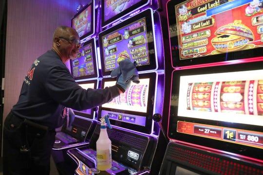 Herbert Allen membersihkan salah satu mesin slot pada hari Minggu, 15 Maret 2020, di Kasino Greektown di Detroit sebelum penutupan coronavirus di Michigan.