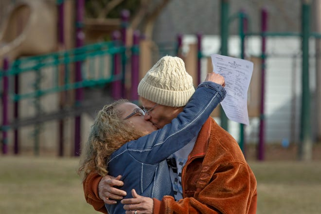 Newlyweds April  and Dormon Page, of Roseville, Michigan, embrace shortly after getting married at Geary Park in Ferndale, Michigan, on Monday, March 16, 2020. The couple had planned to get married in Las Vegas, but had to cancel their plans due to the coronavirus.