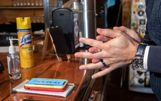 A journalist smears copious amounts of hand sanitizer on before Oakland County Executive David Coulter and Michigan Attorney General Dana Nessel hold a press conference at M-Brew in Ferndale  Monday, March, 16, 2020 to clarify new rules put forth to protect the community from the spread of Coronavirus.