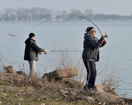 Friends Aleks Huk, right, of Sterling Heights and Andy Deabnski of Clinton Township fish from the shore at Lake St. Clair Metropark in 2018.