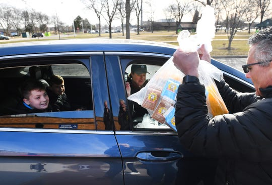 Cheryl Sanborn of Madison Heights with sons Landyn, 12, and Aidyn, 9, pick up bags of breakfast and lunch foods at Lamphere High School in Madison Heights.