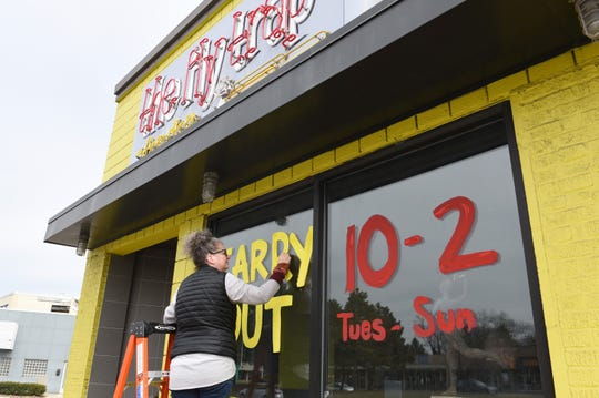 Shannon Jones, manager at the Fly Trap restaurant and bar in Ferndale, paints the windows with the carryout hours during the coronavirus pandemic, March,16, 2020.