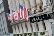 The Wall St. street sign is framed by American flags flying outside the New York Stock Exchange in New York.
