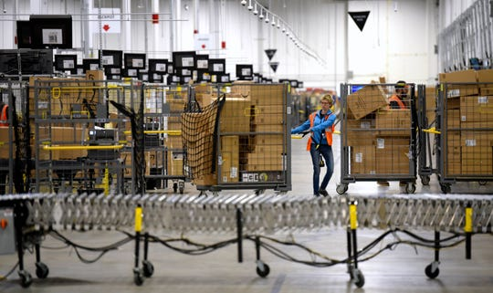 Associates move bins filled with products at the loading dock of Amazon's then-new fulfillment center in Livonia, on March 23, 2018. On Monday, March 16, 2020, Amazon said that it needs to hire 100,000 people across the U.S. to keep up with a crush of orders as the coronavirus spreads and keeps more people at home, shopping online.