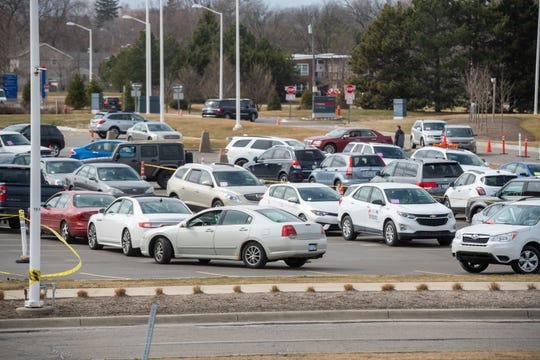 Dozens of cars wait in line to be seen by medical staff during a drive-up screening process at Beaumont hospital in Royal Oak, March 16, 2020. Members of the public concerned that they may be infected with the coronavirus were able to get screening done from their vehicles.