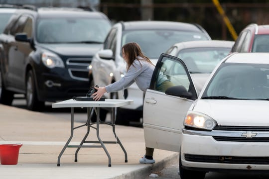 Parents and students pick up laptops during a drive-up process at North Farmington High School, March 16, 2020. Families stayed in their vehicles and laptops were left on a table one at a time so that families could maintain a safe distance from each other.