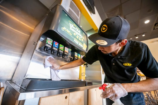Assistant manager Elijah Martinez wipes down and sterilizes the counters and public areas of the Which Wich sandwich restaurant in Farmington Hills on Monday.