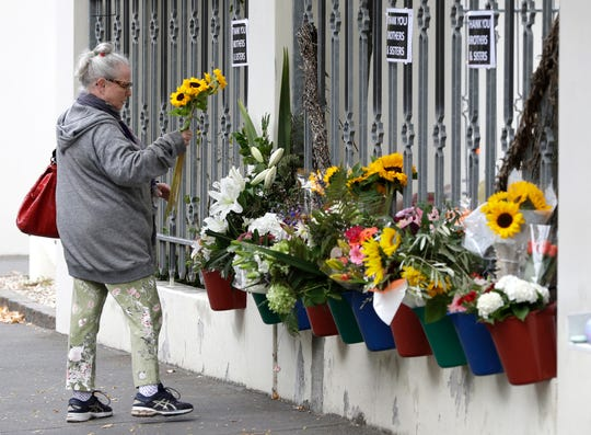A woman prepares to lay flowers outside the Al Noor mosque in Christchurch, New Zealand, Sunday, March 15, 2020. A national memorial in New Zealand to commemorate the 51 people who were killed when a gunman attacked two mosques one year ago has been canceled due to fears over the new coronavirus. (AP Photo/Mark Baker)