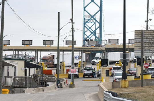Vehicles cross the Ambassador Bridge into Detroit from Windsor, Ontario, on Monday. President Donald Trump said the border will close to non-essential traffic.