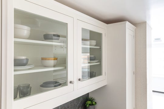 Freshly washed dishes line the shelves of glass front kitchen cabinets.