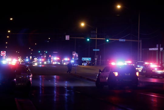 Police cars surround a gas station after a shooting in Springfield, Mo., late Sunday.
