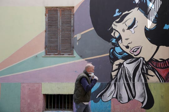 A man adjusts his face mask as he walks past a mural of a crying woman in Rome's Trullo neighborhood, Monday.