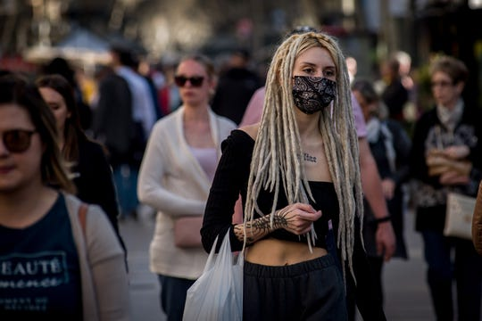 A woman wearing a protective face mask walks Las Ramblas in Barcelona, Catalonia on March 13, 2020.