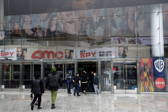 People enter an AMC theater March 14, 2020, in Los Angeles.