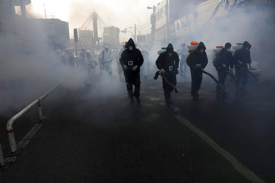 Firefighters disinfect a street against the new coronavirus, in western Tehran, Iran, Friday, March 13, 2020.