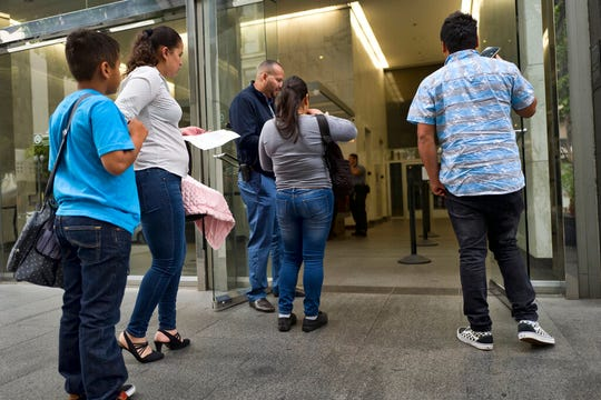 In this May 30, 2019, file photo, immigrant families show paperwork to enter an immigration court in an office building in downtown Los Angeles. Immigration judges, lawyers and union employees want the the U.S. Justice Department to close every immigration court in the country.