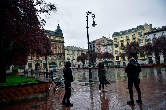 Spanish policemen speak to a resident walking at Plaza de San Francisco square, in Pamplona, northern Spain, Monday.