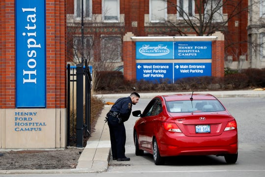 A Police Authority officer screens visitors before entering Henry Ford Hospital in Detroit, Monday, March 16, 2020.