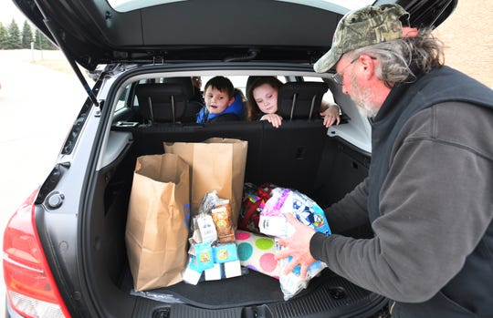 Walled Lake Community School District food service employee Kevin Lawrence puts groceries in the back of the car of Angel Boggs, Walled Lake, as James Boggs, 5 and Olievia Cahoon, 7, look on.