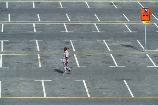A parking lot attendant walks through a typically full parking lot now largely empty over people staying home due to the worldwide coronavirus pandemic in Dubai, United Arab Emirates, Monday, March 16, 2020.