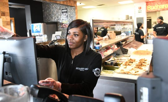 Mariah Jackson, 19, waits on a take out customer at Bucharest Grill on Piquette Street in Detroit on Monday, March 16, 2020. Like other restaurants in Michigan, Bucharest Grill is closing their dine-in area but is still providing take out orders.