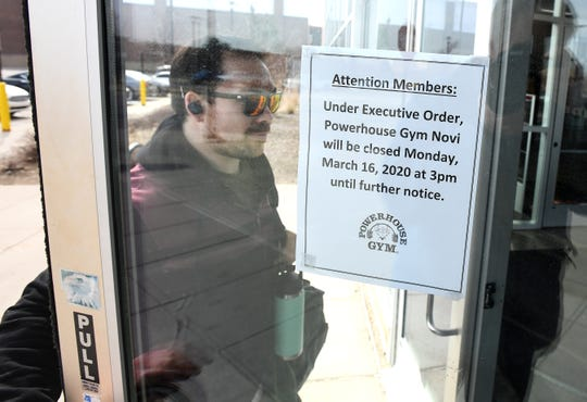Thomas Deschamps of Farmington Hills makes his way into Powerhouse Gym in Novi for one last workout a few hours before the public gym and all others in the state of Michigan close at 3 p.m.  Monday by executive order of Gov. Gretchen Whitmer.