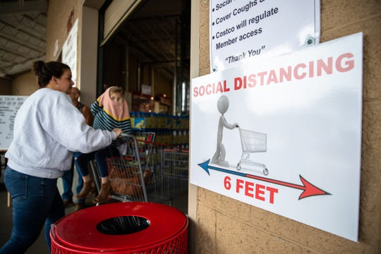 Shoppers enter the Costco in Greenville, SC, past a sign reminding customers of social distancing Monday, March 16, 2020. Grocery stores nationally have been experiencing higher than usual traffic as a result of the coronavirus pandemic.