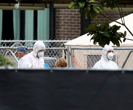 Men wearing protective gear are seen inside the quarantine area at Dobbins Air Reserve Base on Sunday in Marietta, Ga., where Grand Princess cruise ship passengers are isolated in a housing area.