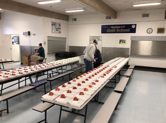 Box Elder Junior High and High School Principal Curt Leeds, Food Service Supervisor Stacy Jones and Food Service staff member Annie Morsette prepare 400 meals for Box Elder students amid school closures. The school will continue to provide meal service for the remainder of the year.