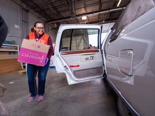 Deanna Elkins, Indianapolis, volunteered by load boxes of food into cars at Gleaners Food Bank of Indiana, Monday, March 16, 2020. The food bank set up a drive-thru distribution system at their westside facility in Indianapolis to enable the distribution of food.
